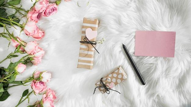 Papier près d'un stylo, cadeaux et fleurs fraîches sur une couverture en laine Photo gratuit