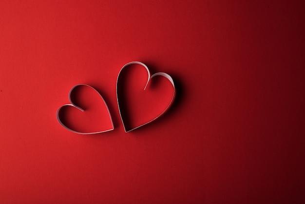 Papier red hearth sur fond rouge Photo gratuit
