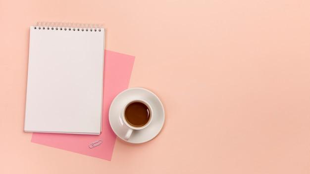 Papier rose, bloc-notes en spirale et tasse à café sur fond de couleur pêche Photo gratuit