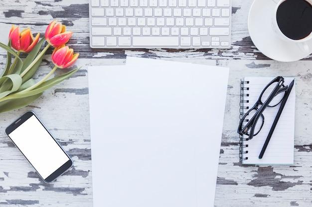 Papier et smartphone avec écran vide près du clavier et tasse à café Photo gratuit