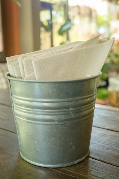 Papier de soie dans un seau sur une table en bois Photo Premium
