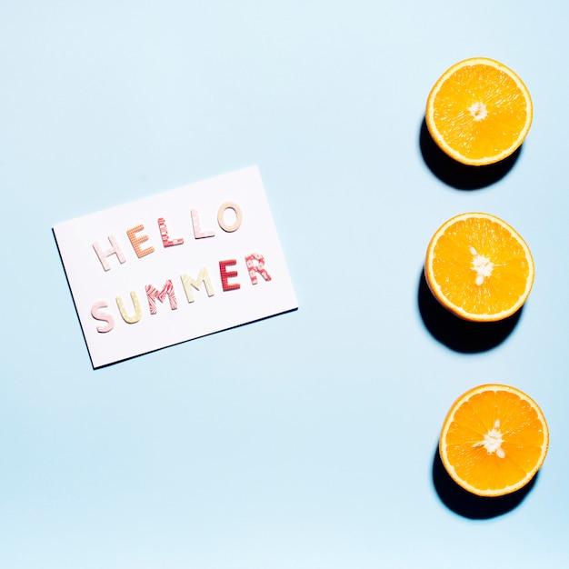 Papier avec texte hello summer avec des moitiés d'oranges juteuses Photo gratuit