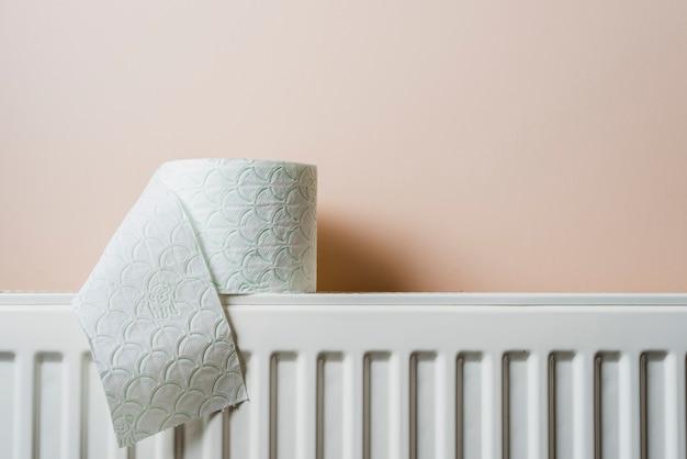 Papier toilette blanc sur radiateur contre mur Photo gratuit