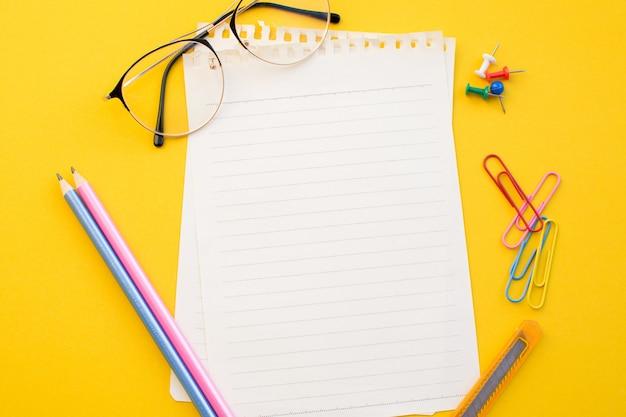 Papier vide de lunettes de cahier et un crayon sur fond de couleur. Photo Premium