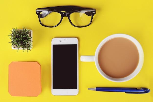 Papier vide avec tasse de café en plastique, stylo, téléphone et lunettes Photo Premium