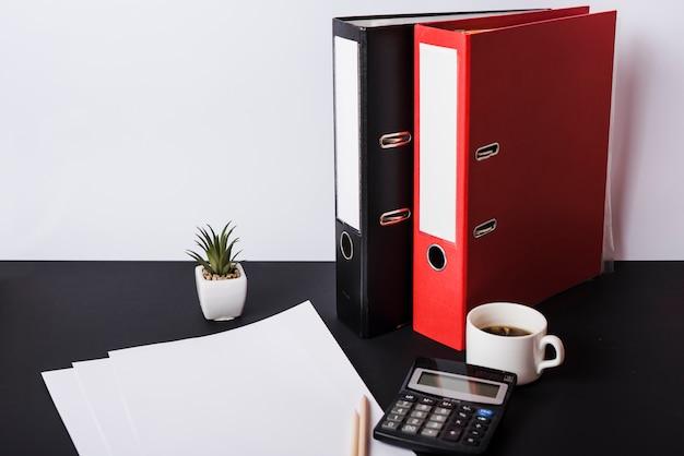 Papier vierge; des crayons; calculatrice; tasse à café et dossiers sur le bureau noir Photo gratuit