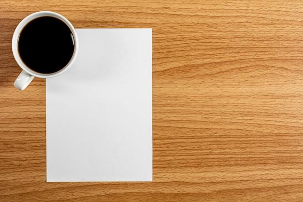 Papier vierge et une tasse de café sur le bureau en bois. - espace vide pour le texte publicitaire. Photo Premium