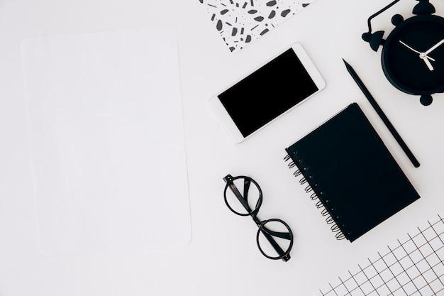 Papier vierge; téléphone intelligent; lunettes; journal intime; crayon et réveil sur le bureau blanc Photo gratuit