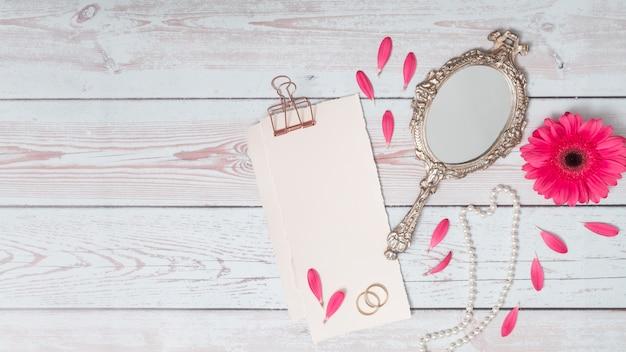 Papiers avec des pétales près de la fleur, des anneaux et un miroir Photo gratuit
