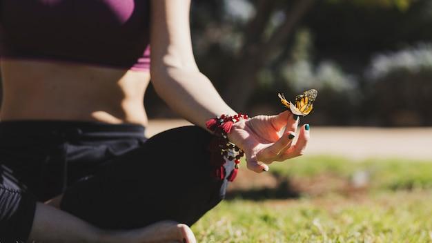 Papillon sur une femme en train de méditer Photo gratuit