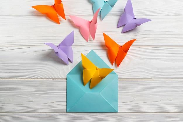 Papillons colorés en papier brillant sortant de l'enveloppe. Photo Premium