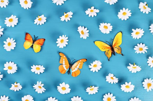 Papillons et marguerites jaunes et orange sur fond bleu. vue de dessus. fond d'été. lay plat. Photo Premium