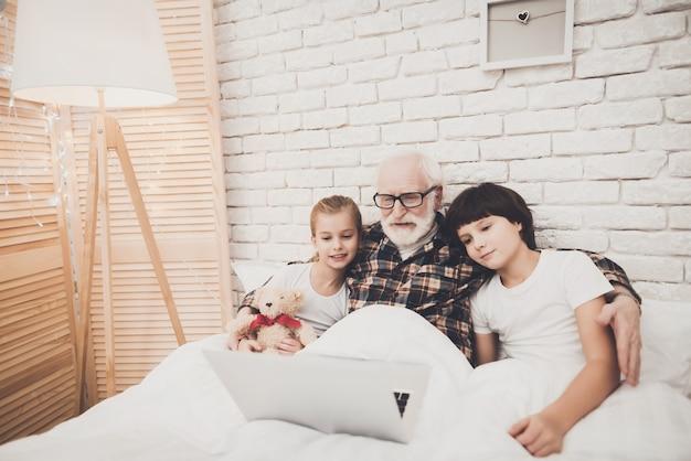 Papy Et Ses Enfants Regardent Des Films Au Coucher. Photo Premium