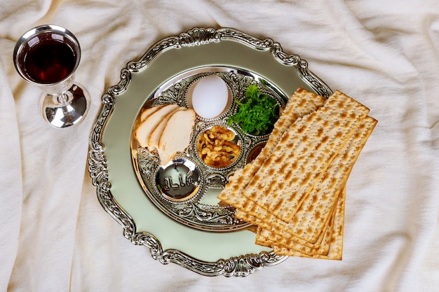 Pâque fond avec bouteille de vin, matzoh, oeuf et assiette de seder Photo Premium