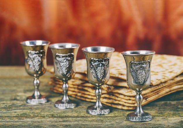 Pâque fond quatre verres vin et pain de fête juif matzoh sur planche de bois. Photo Premium