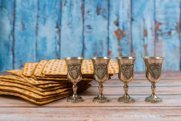 Pâque quatre verres de vin et pain de vacances juif matzoh sur planche de bois. Photo Premium