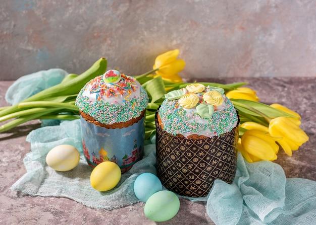 Pâques encore la vie. gâteau de pâques, peint des oeufs avec des tulipes sur un fond en bois ancien rustique. Photo Premium