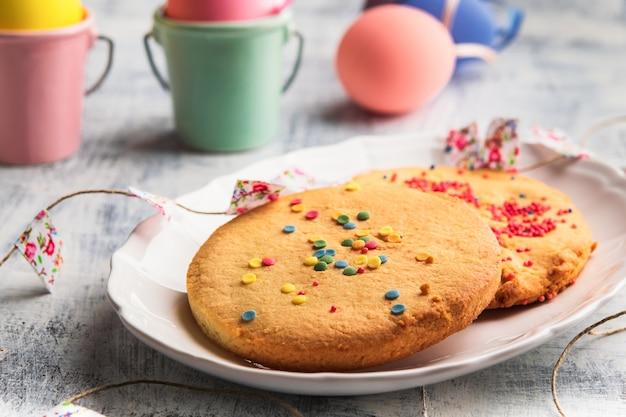 Pâques printemps cookies avec des pépites colorées sur une plaque blanche. heureux concept de pâques. Photo Premium