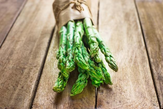 Paquet d'asperges organiques vertes brutes fraîches nouées avec de la ficelle sur la table de cuisine en bois de planche Photo Premium