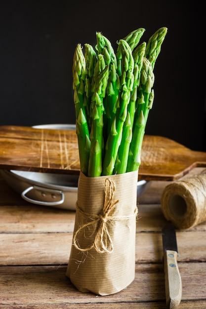 Paquet d'asperges vertes fraîches enveloppées dans du papier kraft ficelé avec de la ficelle debout sur une table de cuisine en bois Photo Premium