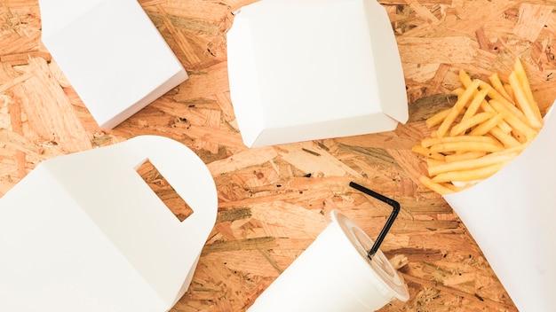 Paquet blanc; boisson jetable et frites sur fond en bois Photo gratuit