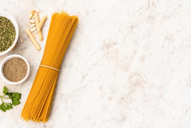 Paquet de pâtes spaghettis non cuits et ingrédient sur fond de marbre Photo gratuit