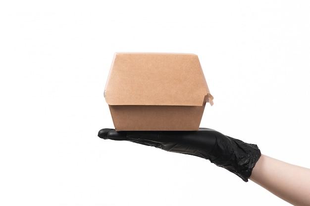 Un Paquet Vue Avant De La Nourriture Dans Des Gants Noirs Tenant Sur Blanc Photo gratuit