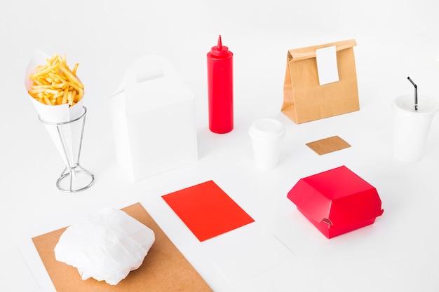 Paquets de nourriture avec des frites et une tasse de disposition sur fond blanc Photo gratuit