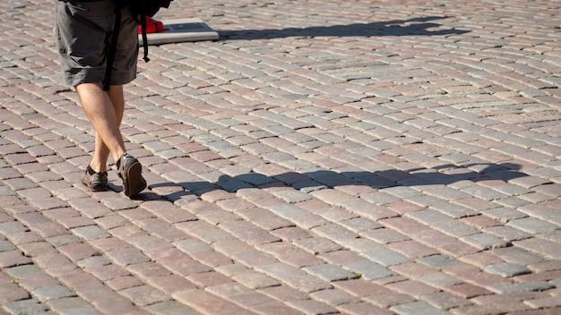 Par Une Journée Ensoleillée, Un Homme Marche Le Long Du Trottoir. Les Ombres Humaines Sont Visibles Sur Le Trottoir. Vue De Dos. Photo Premium