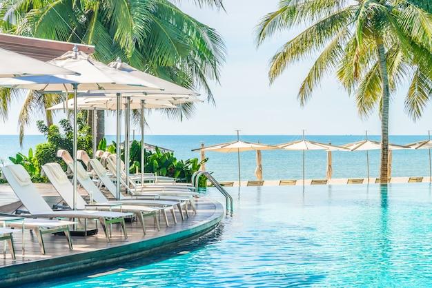 Parapluie avec chaise dans un complexe hôtelier avec piscine Photo gratuit