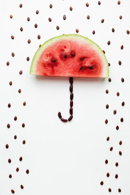 Parapluie de pastèque avec des graines sur fond blanc Photo gratuit
