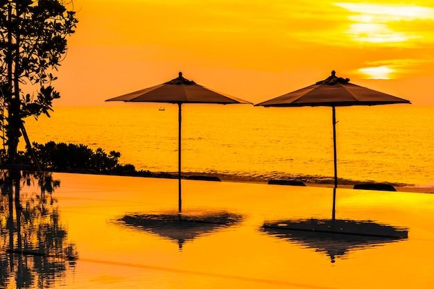 Parasol et chaise autour de la piscine au bord de la mer, au lever ou au coucher du soleil Photo gratuit