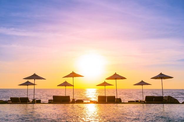 Parasol et chaise autour de la piscine de l'hôtel pour des voyages de loisirs et des vacances Photo gratuit
