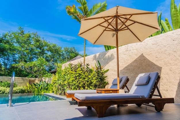 Parasol et chaise autour de la piscine près de la mer, plage de l'océan avec ciel bleu et nuage blanc Photo gratuit