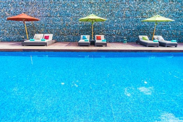 Parasol et chaise autour de la piscine Photo gratuit