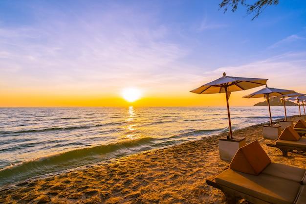 Parasol et chaise avec oreiller autour du magnifique paysage de plage et de mer Photo gratuit