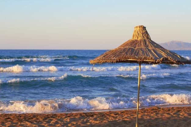 Parasol sur la plage de la mer au coucher du soleil avec des vagues sur le fond. place pour le texte Photo Premium