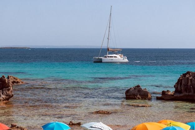 Parasols Sur La Rive Et Un Catamaran Blanc Dans La Mer Au Large De L'île D'ibiza Photo Premium
