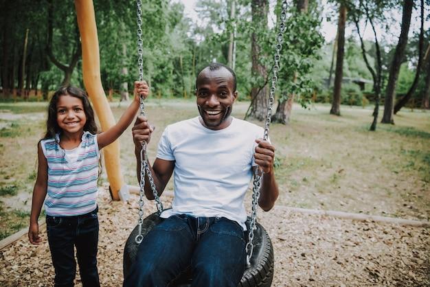 Parc d'attractions papa balançant fille de race mixte. Photo Premium