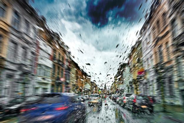 Pare-brise de voiture avec la pluie tombe pendant la tempête et feux de circulation flou Photo Premium