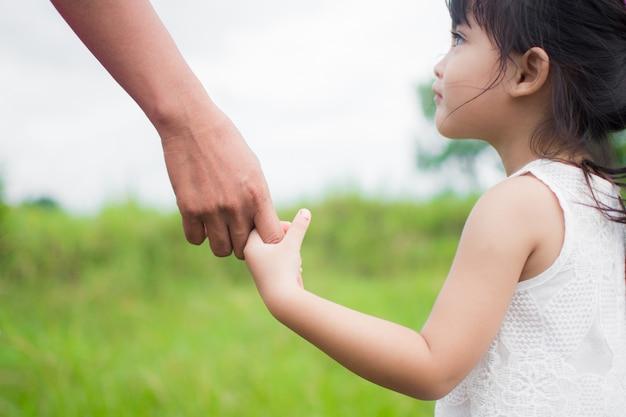 Un parent tient la main d'un petit enfant, nature en plein air Photo Premium