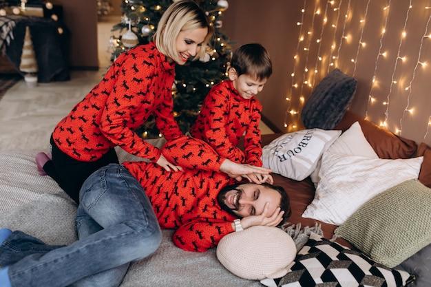 Des parents attirants et leur petit fils en pull rouge s'amusent sur le lit avant un noël Photo gratuit
