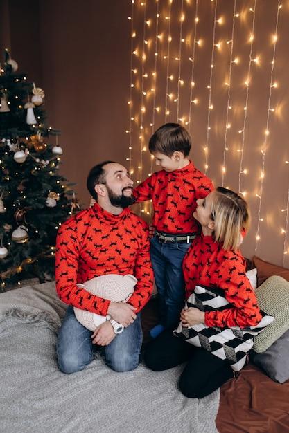 Des Parents Attrayants Et Leur Petit Fils En Pull-over Rouge S'amusent Sur Le Lit Avant Un Christ Photo gratuit