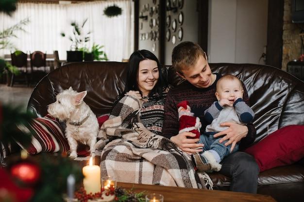 Les Parents Avec Un Bébé à Noël Et Un Chien Assis Sur Le Canapé Photo gratuit
