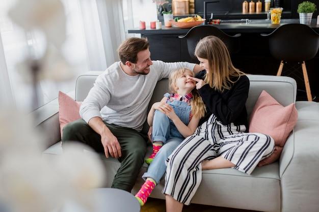 Parents câlins avec une fille sur le canapé Photo gratuit