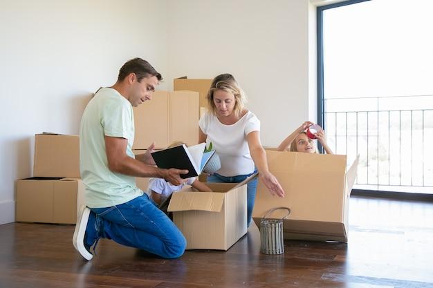 Parents Concentrés Et Enfants Drôles Déballant Des Choses Dans Un Nouvel Appartement, Assis Sur Le Sol Et Prenant Des Objets Dans Une Boîte Ouverte Photo gratuit