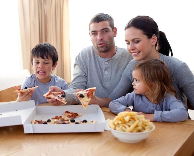 Parents et enfants mangeant des pizzas et des frites sur un canapé Photo Premium