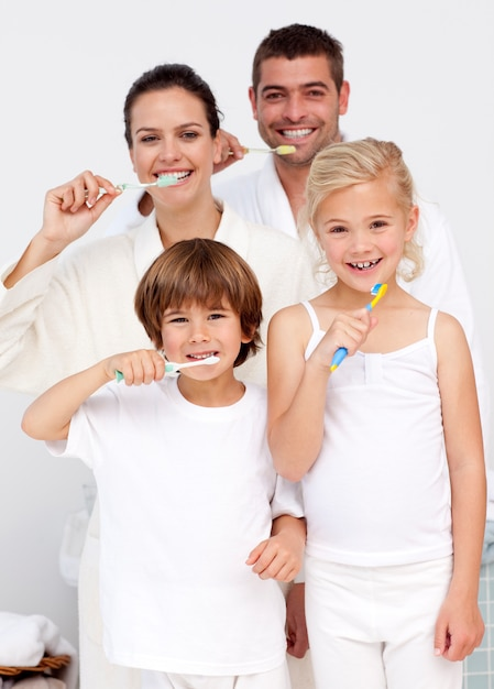 Parents et enfants nettoyant leurs dents dans la salle de bain Photo Premium