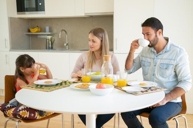 Parents Et Enfants Prenant Leur Petit-déjeuner Ensemble, Buvant Du Café Et Du Jus D'orange, Assis à Une Table à Manger Avec Des Fruits Et Des Biscuits Et Parlant. Photo gratuit