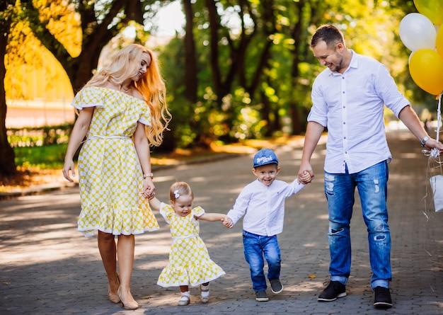 Les parents étonnants s'amusent avec leurs deux enfants marchant dans le parc Photo gratuit